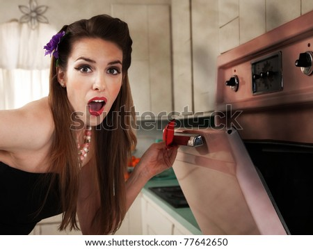 Surprised beautiful Caucasian housewife in kitchen checks her oven - stock photo