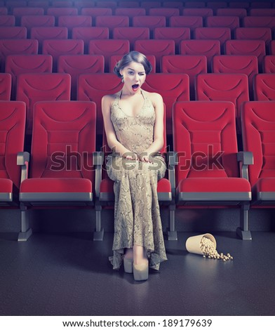 Surprised beautiful girl in an empty cinema. Creative concept - stock photo