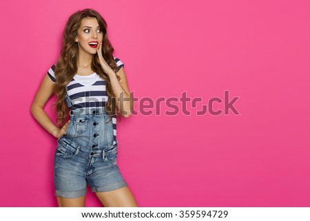 Surprised beautiful girl in dungarees and striped shirt looking at pink copy space and holding hand on chin. Three quarter length studio shot on pink background. - stock photo