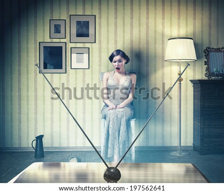 Surprised beautiful girl in the vintage interior,watching tv. Creative concept  - stock photo