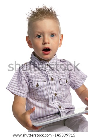 Surprised blond young boy with his mouth open, holding in his hands a tablet pc and looking at the camera isolated on white background