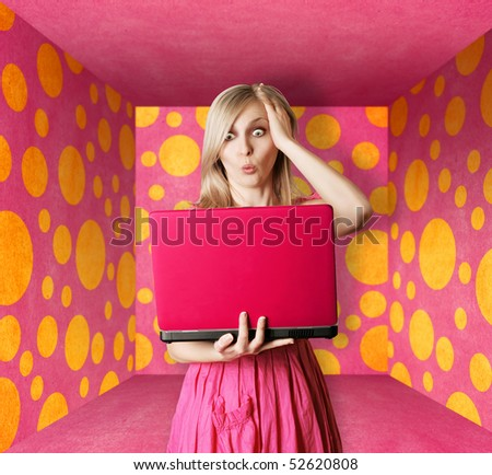 surprised blonde in pink dress with laptop in pink room - stock photo