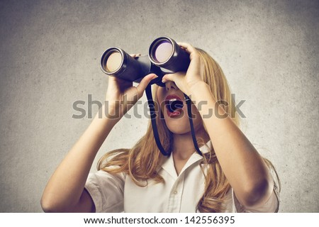surprised blonde woman looking with binoculars - stock photo