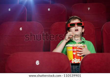 Surprised boy eating popcorn in the movie theater - stock photo