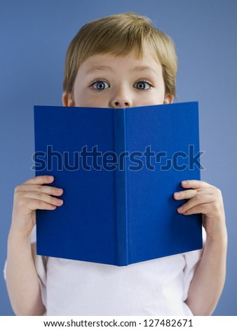 Surprised boy hidden behind a blue hardcover book