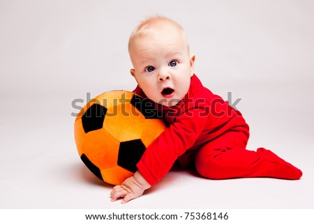 Surprised boy with black and orange soccer ball - stock photo