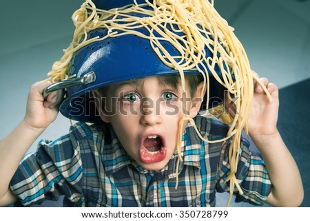 Surprised boy with pasta on the head  - stock photo