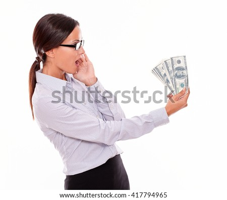 Surprised brunette businesswoman looking at money while she is holding with an impressed gesture of her hand to her face and wearing her straight hair back and button down shirt on a white background - stock photo