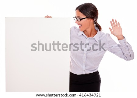 Surprised brunette businesswoman with glasses looking at a placard with her open mouth, wearing her straight hair tied back and a button down shirt, gesturing with her left hand in the air - stock photo