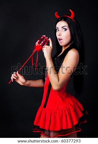 surprised brunette girl wearing a halloween costume of an imp - stock photo