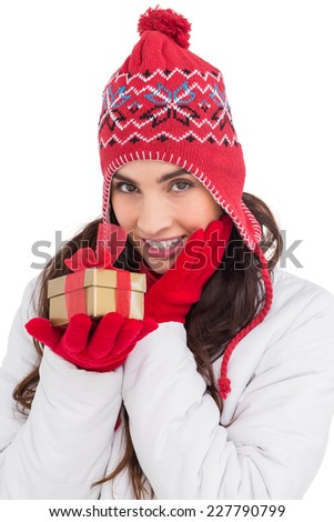 Surprised brunette in winter clothes holding gift on white background
