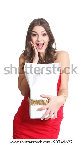 Surprised brunette with a gift in her hand - stock photo