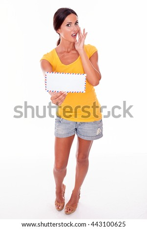 Surprised brunette woman holding a blank envelope and touching her mouth while looking at camera wearing a yellow t-shirt and short jeans isolated - stock photo