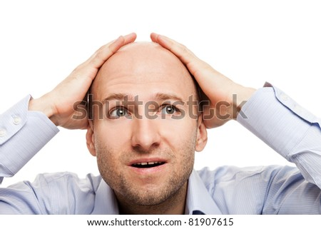 Surprised business man hand holding bald shaved head - stock photo