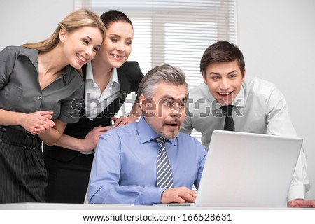 Surprised business team looking on laptop with laughing. Having fun at working place.  - stock photo