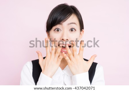 Surprised business woman against pink background - stock photo