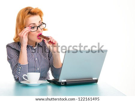 Surprised business woman eating cookie on work, isolatd on white. Studio shot - stock photo