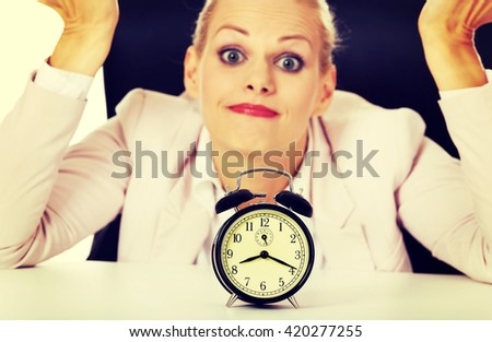 Surprised business woman lsitting behind the desk with alarm clock - stock photo