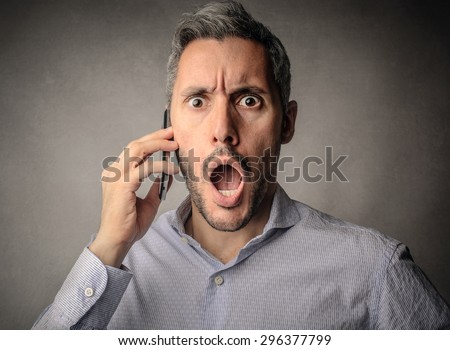 Surprised businessman doing a phone call - stock photo