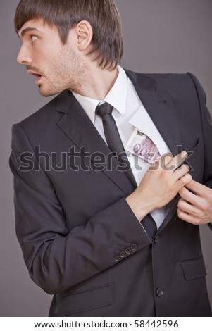 surprised businessman hiding money in his jacket - stock photo