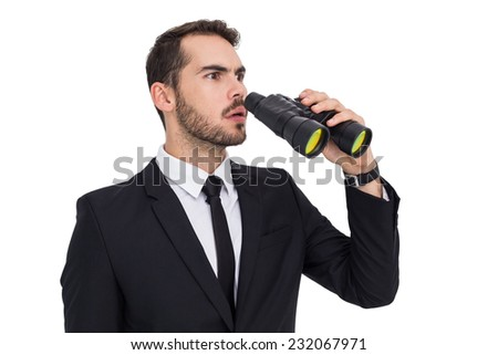 Surprised businessman standing and holding binoculars on white background
