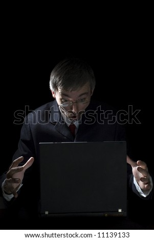 surprised businessman with a laptop isolated on black