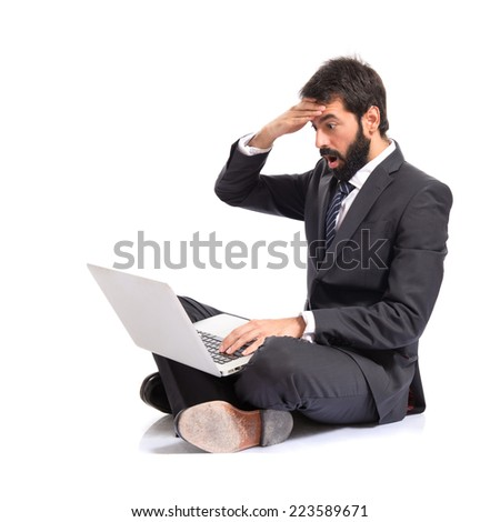 Surprised businessman with laptop over white background