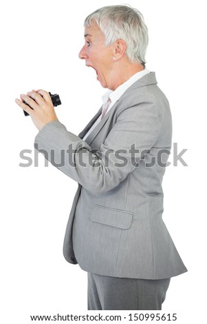 Surprised businesswoman holding binoculars on white background