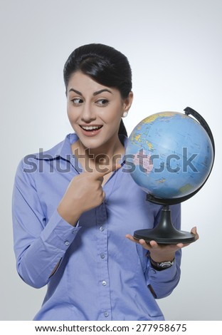 Surprised businesswoman pointing at globe against gray background - stock photo