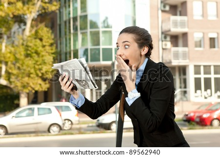 surprised businesswoman reading newspaper and  holding hand on mouth - stock photo