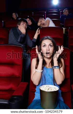 Surprised by the girl at the cinema - stock photo