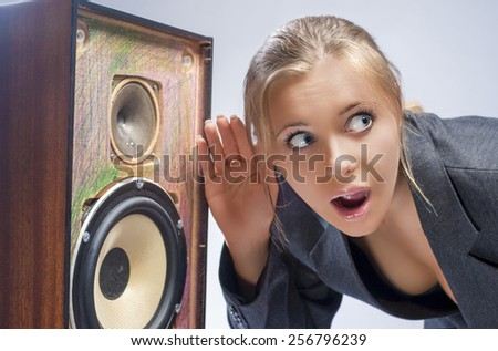 Surprised Caucasian Blond Female Harkens to Outdated Loudspeaker in Studio. Horizontal Image - stock photo