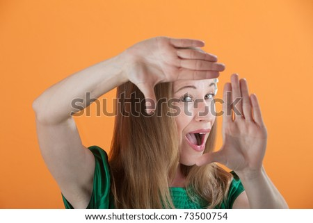Surprised Caucasian woman framing her face on an orange background - stock photo