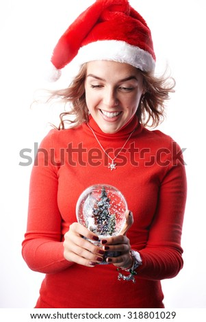Surprised cheerful smiling Christmas young woman holding snow globe over white background