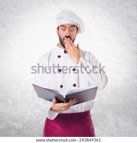 Surprised chef reading a book - stock photo