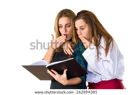 Surprised chefs reading a book  - stock photo