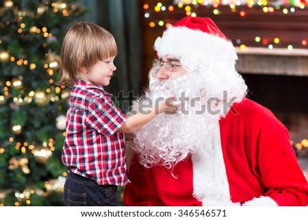Surprised child boy looks at fake Santa Claus with fake beard sitting opposite Christmas tree - stock photo