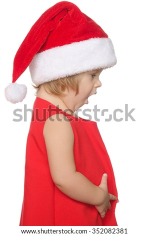 surprised child in christmas cap isolated on white - stock photo