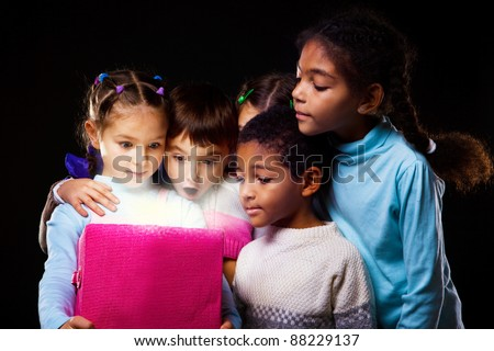 Surprised children looking into the shining box - stock photo