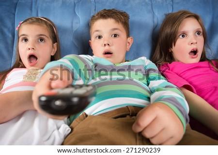 Surprised children watching TV - stock photo