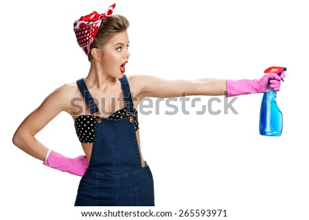 Surprised cleaning girl wearing pink rubber protective gloves holding spray / young beautiful American pin-up girl isolated on white background. Cleaning service concept - stock photo