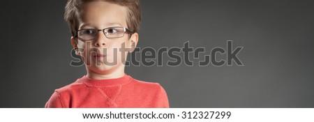 Surprised contemplating little boy in glasses solving a problem. Studio shot portrait over gray background. Fashionable little boy. - stock photo