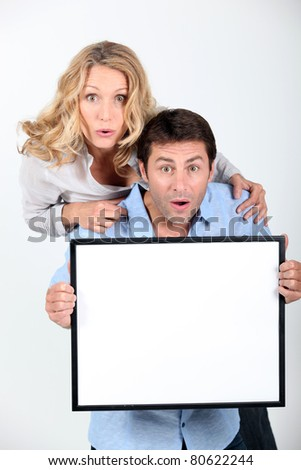 Surprised couple holding blank message board
