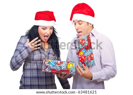 Surprised couple screaming of what they found in the Christmas box isolated on white background - stock photo