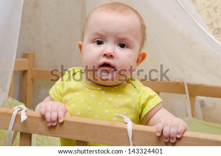 surprised cute baby  standing in a crib