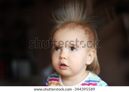 Surprised cute child (boy) with fun face and hair stood on end, indoor portrait