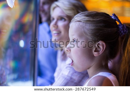 Surprised daughter behind a starfish tank at the aquarium - stock photo