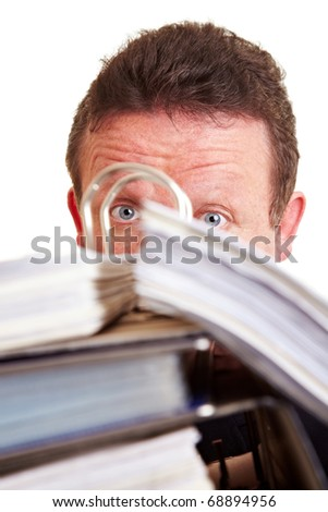Surprised elderly business manager hiding behind files