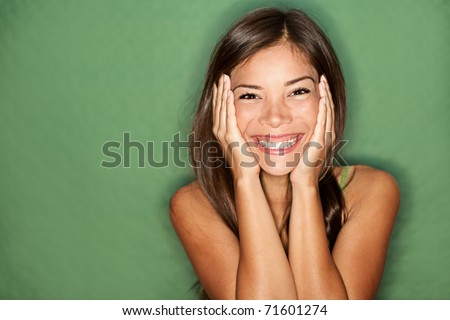 Surprised excited woman on green background. Cheerful multiracial Asian / Caucasian female model joyful. - stock photo