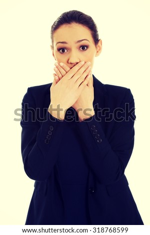Surprised excited young business woman covering her mouth.